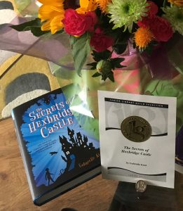 Junior Library Guild certificate and pin for The Secrets of Hexbridge Castle